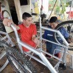 Detentos transformam bicicletas fora de uso em cadeiras de rodas.